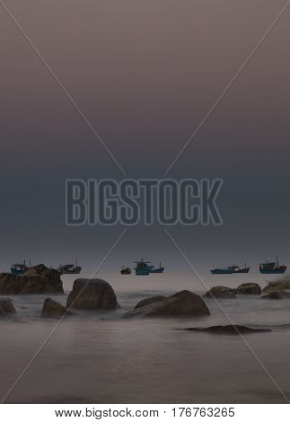 A rocky coastline morning glow looking out over the south China sea in Vung Lam Bay Vietnam. With rock and fishing boat silhouettes.