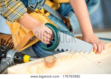 Close-up partial view of little boy sawing wooden plank with toy saw