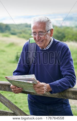 Senior Man Hiking In Countryside Looking At Map
