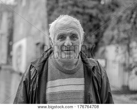 KUTAISI, GEORGIA, NOVEMBER, 05: Local old man with gray hair and wrinkes, walking in a georgian park in Kutaisi on nowember, 05, 2016 in Georgia