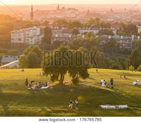 POLAND, KRAKOW- JULY 03: Lovely busy park full of students resting late in the evening, sunset in Krakow Poland on July 03, 2015