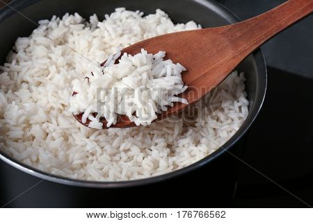 Cooked rice in saucepan with spoon
