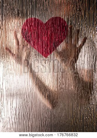 Hands of young couple with heart behind riffled glass poster
