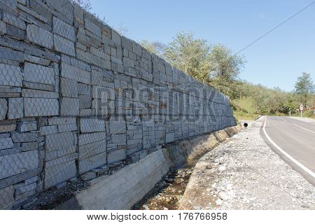 Stone wall at the road. Abstract background part of a fence