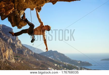 Young man struggling to climb ledge on cliff view of coast below