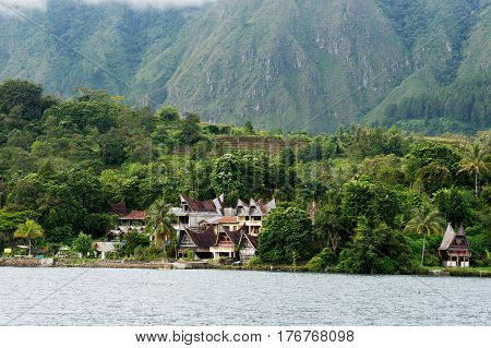 Several houses build at the foot of a mountain next to ta lake in Sumatra Samosir Island in the afternoon Indonesia.