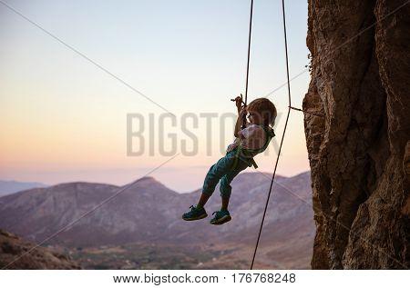 Little boy rock climber being lowered down