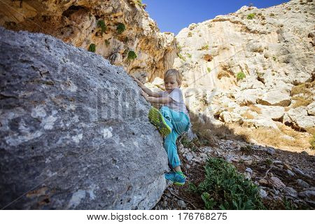 Little boy climbing natural boulder in climbing sector