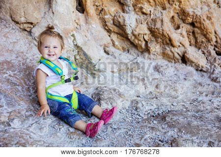 Happy little girl wearing safety harness and sitting at cliff