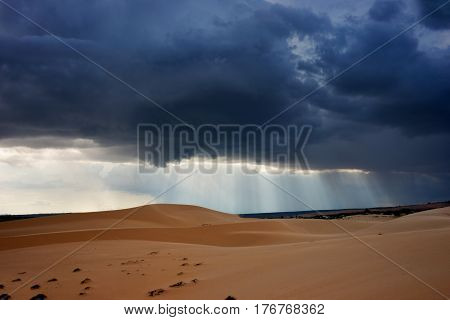 Dark black storm clouds with piercing sunrays covering desert landscape at midday in Vietnam.