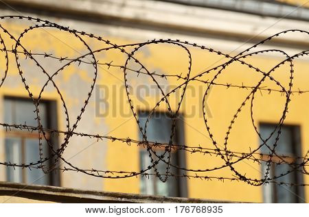 Barbed wire on a fence to protect the area from penetration of the thief .