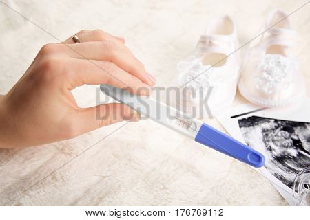 Pregnancy test in hand and ultrasound photo of baby on white fluffy background