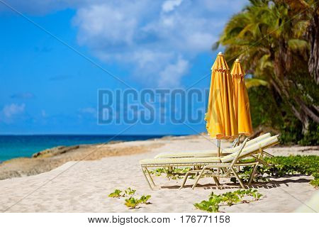 sunbeds and umbrellas at beautiful caribbean beach with white sand palms turquoise water and blue sky
