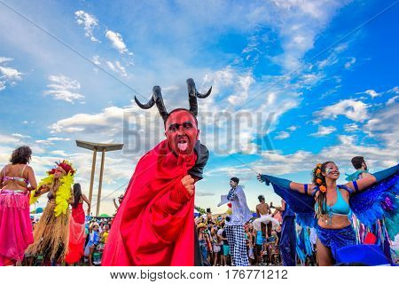 RIO DE JANEIRO, BRAZIL - FEBRUARY 28, 2017: Young man on stilts in a costume of devil with red face, big black horns and black and red cloak licking his tail at Bloco Orquestra Voadora, Carnaval 2017