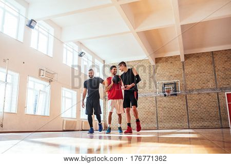 Shot of basketball players practicing on the basketball court.