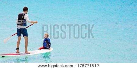 panorama of family of two enjoying stand up paddleboarding at caribbean vacation active and healthy lifestyle