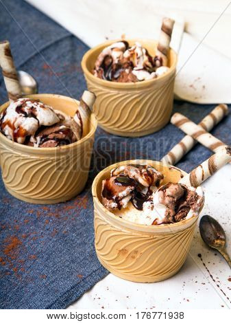 Delicious ice cream in a cup with chocolate sauce cream rolls