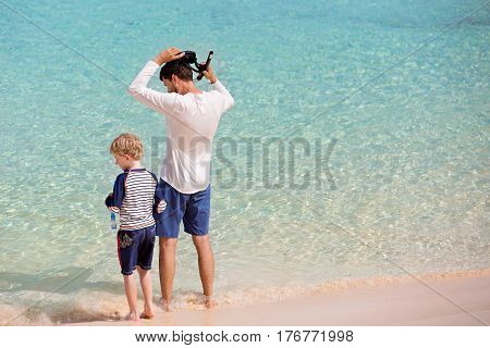 back view of family of two father and son ready for snorkeling healthy activity at tropical island summer vacation concept