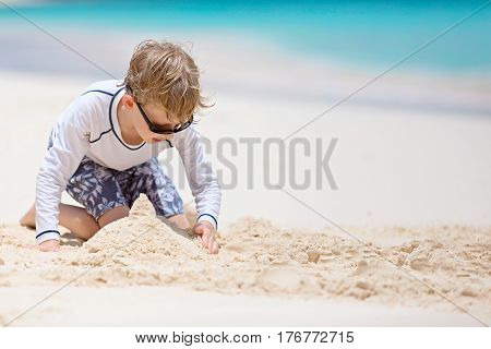 little boy in sunglasses and rashguard building sandcastle at the perfect caribbean beach
