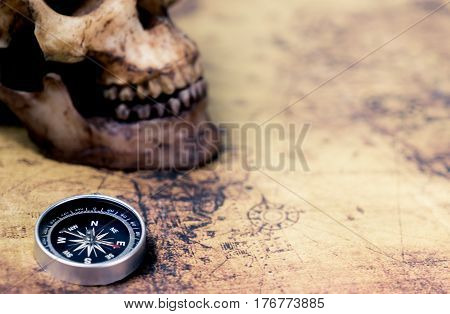 Compass and Dead Skull on vintage map for treasure hunter concept with copy space