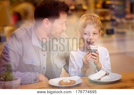 family of two father and son spending time together and enjoying desserts in cafe