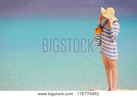 standing young woman enjoying the perfect caribbean beach during summer vacation copyspace on the left