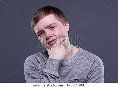 Skeptical blond young man on gray background