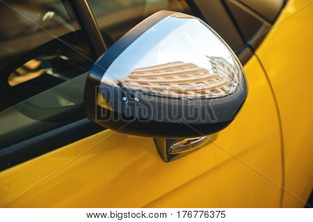 Reflection in the yellow car chrome rear-view mirror of a French building