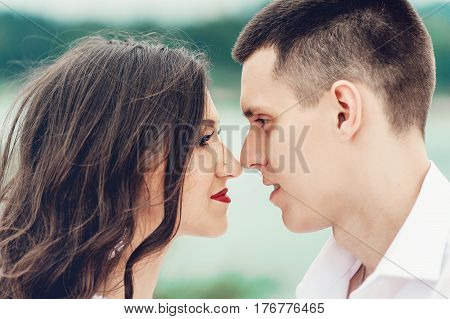 Close up portrait of kissing couple against green trees in the park. Beautiful young woman with long dark wavy hair kissing handsome man outdoors. Cute newlyweds on their wedding ceremony.