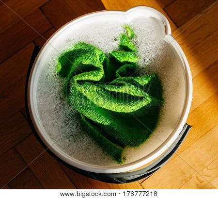 Square image - view from above of a bucket full with water and washing cloth ready to clean the wooden parquet or any other home surface