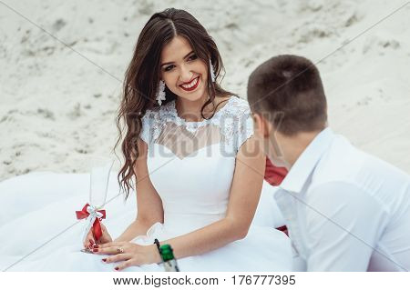 Happy smiling newlyweds drinking champagne on the sunny beach on their wedding day. Newlyweds sitting on the beach, having fun and drinking wine. Beautiful woman and handsome man.