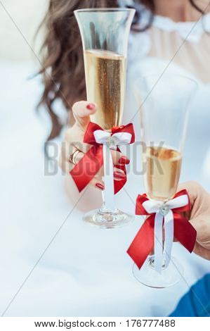 Newlyweds drinking champagne on their wedding day. Luxury wedding glass in newlyweds hands. Bride and groom holding glasses in hands with alcohol drink on the wedding ceremony.