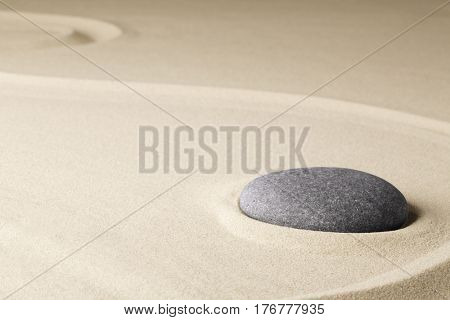 Meditation stone in a Japanese zen garden, background concept for purity harmony balance simplicity and relaxation.