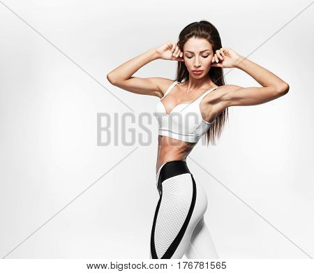 Beautiful slender brunette on white background in white sportswear