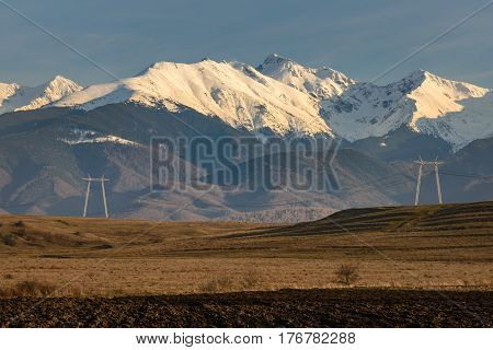 High voltage power towers and lines with snowy peaks of Fagaras Mountains in background a a plowed field in foreground. Horizontal view with warm tones of afternoon sunlight and blue sky.