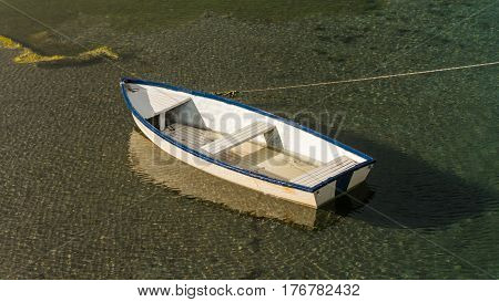 White wooden boat with a blue stripe floating in clear and transparent water with afternoon sunlight