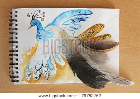 Photo of a colored watercolor illustration on a notebook. Picture of an unusual peacock with a tail of real feathers.