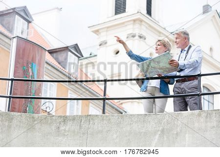 Middle-aged woman showing something to man while reading map by railing
