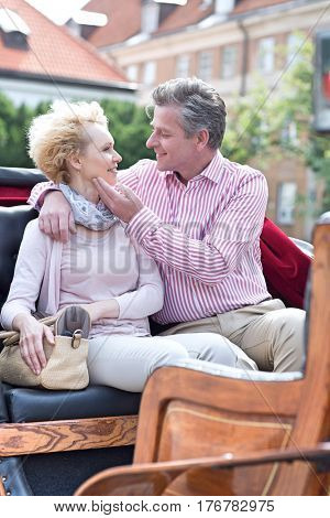 Romantic middle-aged couple sitting in horse cart
