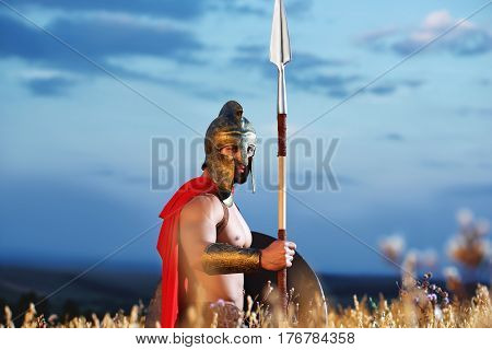 Front view of confident warrior wearing iron helmet and red cloak holding sword in hand. Soldier wearing like spartan or antique roman looking at camera, posing at field. Dark dramatic sky.