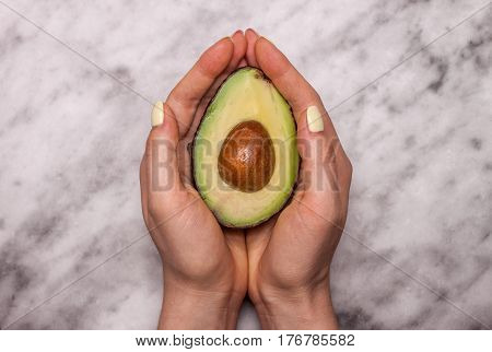 female hands keeping cut avocado on marble background