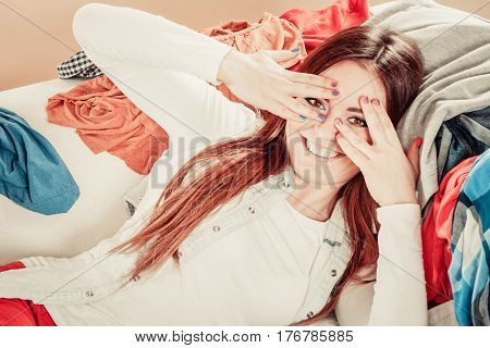 Playful happy gesture with hands. Young smiling woman cover face with hands see through fingers.