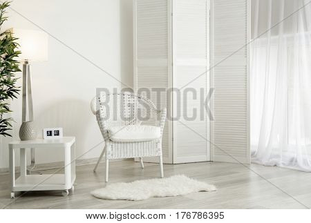 Interior of beautiful room with folding screen and armchair