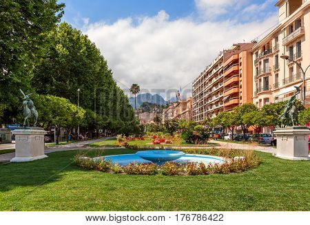 MENTON, FRANCE - JULY 07, 2012: View of green urban park along street and colorful buildings in center of Menton - small town on French Riviera, famous for its gardens and annual lemon festival.