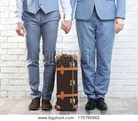 Happy gay couple with suitcase on brick wall background