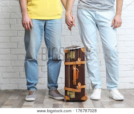 Happy gay couple with suitcase, passports and tickets on brick wall background