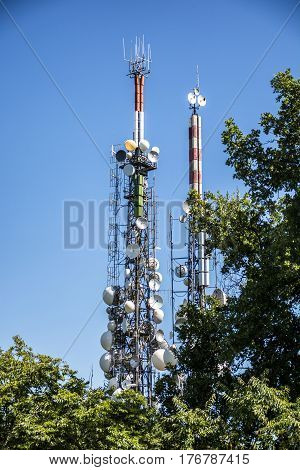 Tower of radio and TV broadcasting antennas behind trees against clear blue sky
