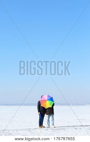 Happy gay couple with colorful umbrella, outdoors