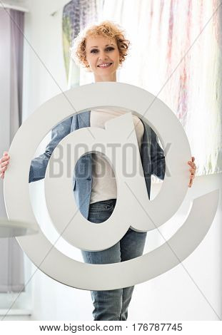 Portrait of confident businesswoman holding at sign in creative office