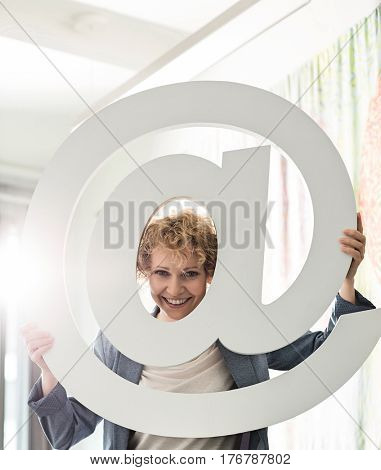 Portrait of happy businesswoman looking through at sign in creative office